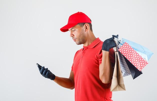 Uomo di consegna che tiene i sacchetti di carta e guardando smartphone in uniforme rossa, guanti.