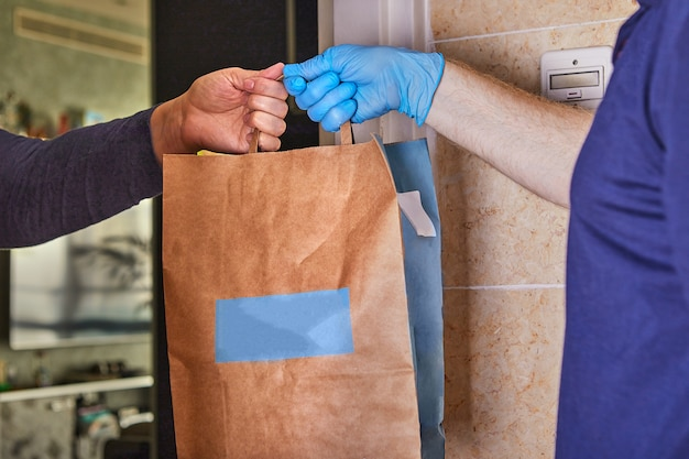 Delivery man holding paper bags in medical rubber gloves. quarantine. coronavirus. copy space. fast and free transport delivery. online store and express delivery.