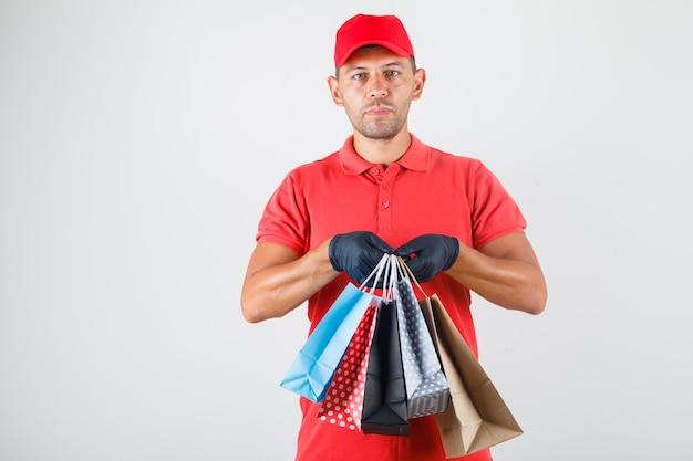 Uomo di consegna che tiene i sacchetti di carta in uniforme rossa, vista frontale dei guanti.