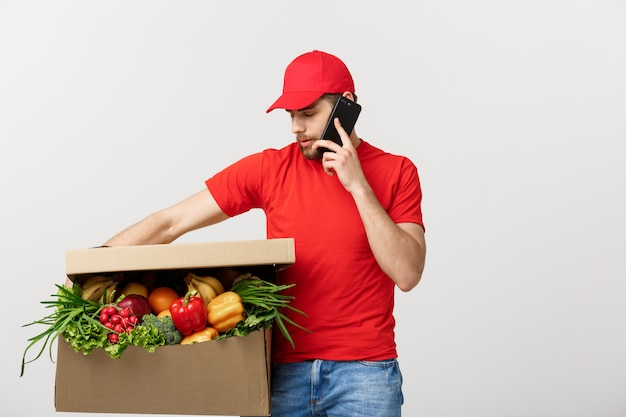 Delivery man holding paper box with food and making a call with mobile phone