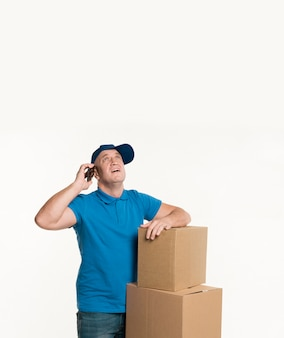 Delivery man holding phone and looking up