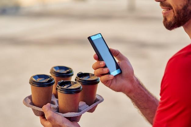 Доставщик, держащий смартфон и кофейные чашки на доске доставки на открытом воздухе, обрезанный. концепция доставки еды