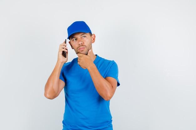 Uomo di consegna che tiene smartphone vicino all'orecchio in maglietta blu