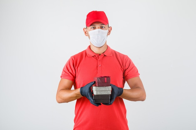 Delivery man holding stack of gift boxes in red uniform, medical mask