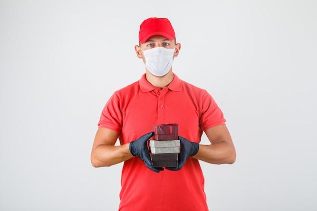 赤い制服、医療マスクのギフトボックスのスタックを保持している配達人