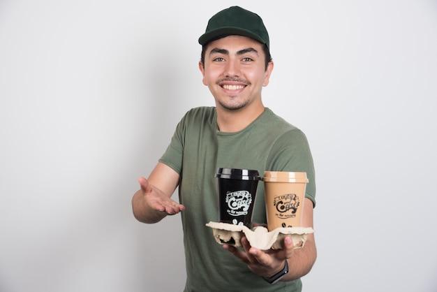 Uomo di consegna che tiene tazze da asporto di caffè su sfondo bianco.