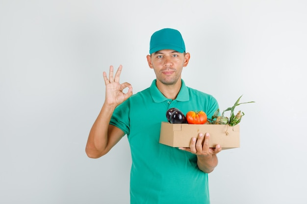 Delivery man holding vegetable box with ok sign in green t-shirt and cap