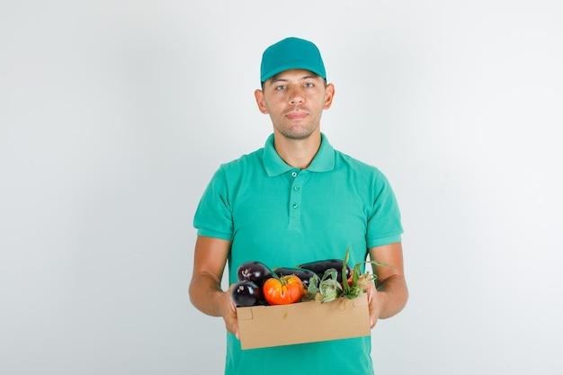 Доставщик, держащий овощи в картонной коробке в зеленой футболке и кепке