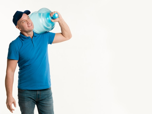 Delivery man holding water bottle with copy space