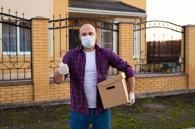 配達人は段ボール箱を保持し、コロナウイルス防止のためにフェイスマスクを着用