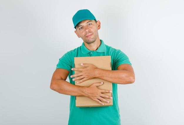 Delivery man hugging cardboard box in green t-shirt with cap