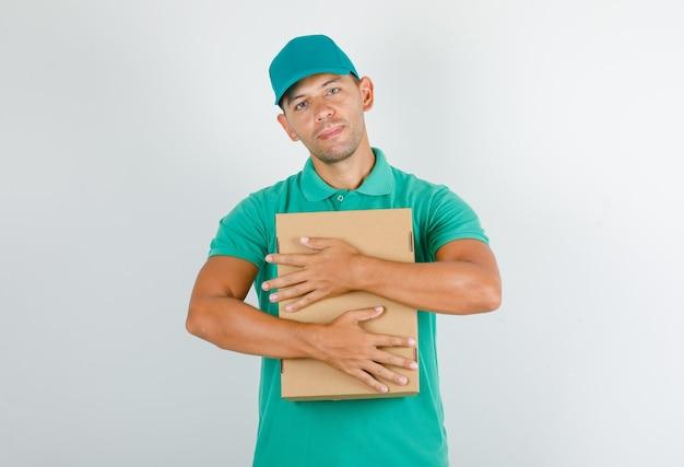 Доставщик обнимает картонную коробку в зеленой футболке с кепкой