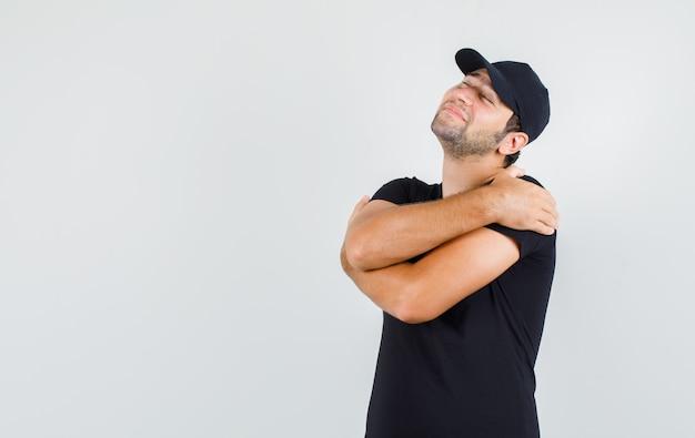 Uomo di consegna che si abbraccia in maglietta nera
