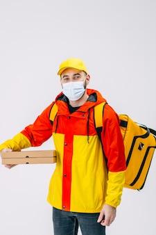 흰색 표면에 서서 골판지 상자를 들고 의료 마스크 배달 남자 피자 카메라를보고 남성 택배