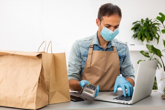 Курьер в защитной маске и перчатках держит в руке pos-терминал. сервисный карантин концепция вируса пандемии коронавируса