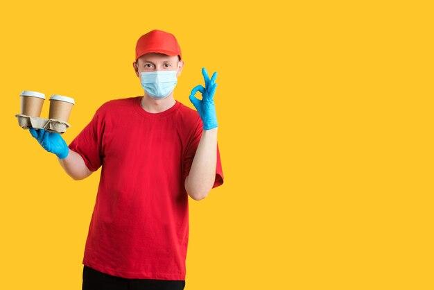 赤い帽子とtシャツを着た配達員がマスクと手袋を着用し、エコカップのコーヒーを飲んで大丈夫な兆候を示しています