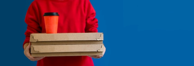 赤いtシャツを着た配達員、食べ物を注文し、青い背景に2つのピザボックスとコーヒーのグラスを持っています