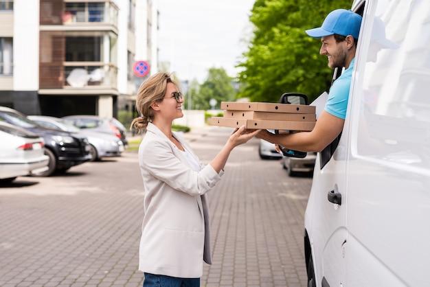 흰색 밴에 있는 배달원은 여성 고객에게 피자를 배달합니다.
