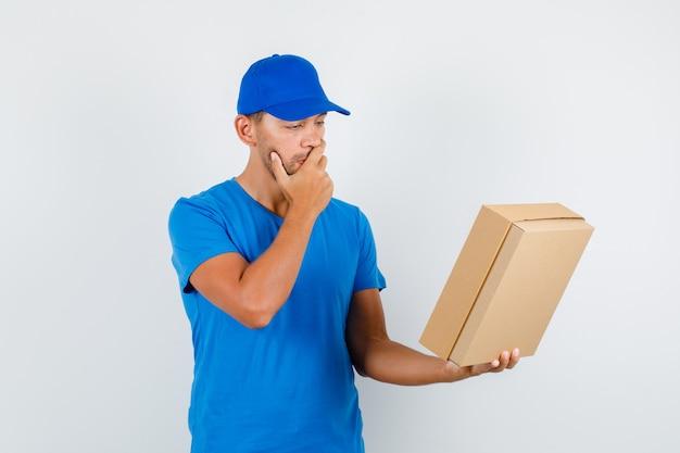 Курьер в синей футболке, кепке держит картонную коробку рукой во рту и задумчиво смотрит