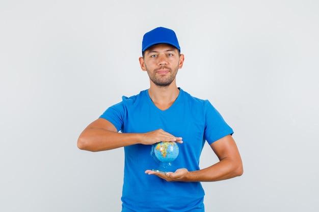 파란색 티셔츠에 배달 남자, 모자 글로브를 들고 긍정적 인 찾고