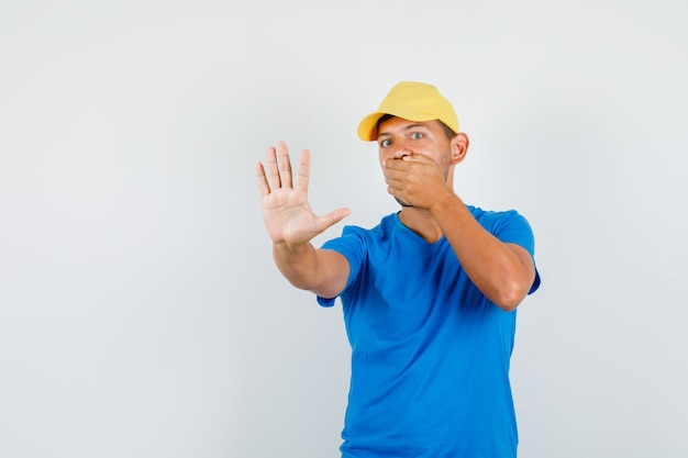 青いtシャツの配達人、ジェスチャーなしで口に手を保持し、怖がって見えるキャップ