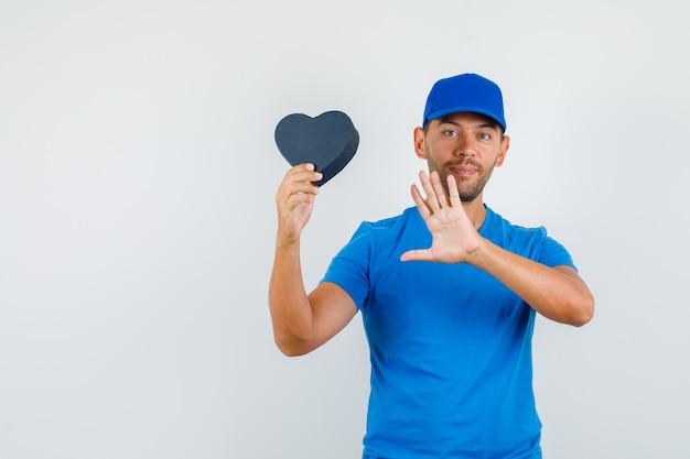 青いtシャツの配達人、手のひらを見せて陽気に見える間、プレゼントボックスを保持しているキャップ