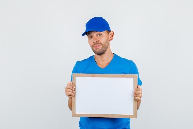 Курьер в синей футболке, кепке держит белую доску и выглядит веселым