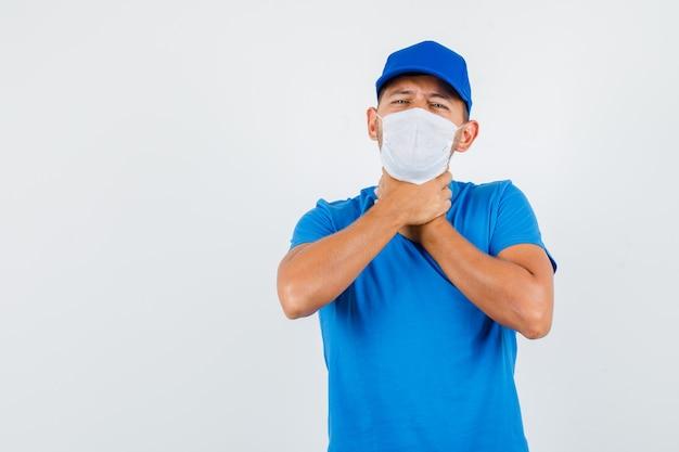Курьер в синей футболке, кепке, маске страдает от боли в горле и выглядит больным