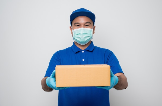 Доставщик в синей форме в защитной маске, отдавая картон посылки клиенту.