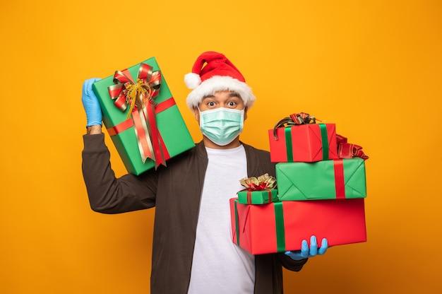 Экспедитор в рождественской форме держит подарочную коробку и носит маску и медицинские резиновые перчатки.