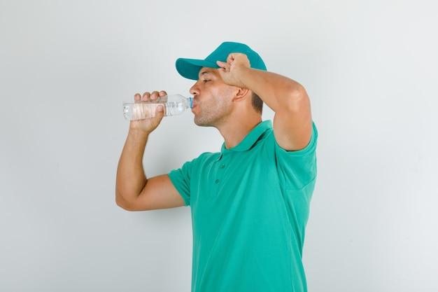 Доставщик в зеленой футболке и кепке пьет воду и выглядит жаждущим