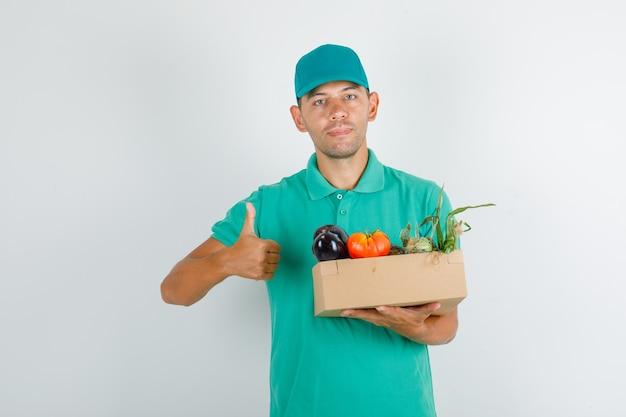 Доставщик в зеленой футболке и кепке держит коробку с овощами с большим пальцем вверх