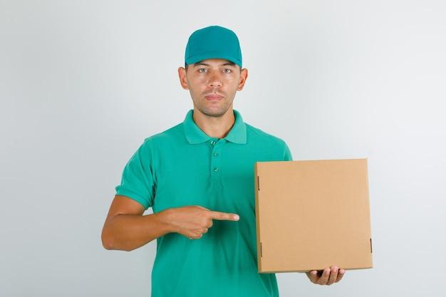 Доставщик в зеленой футболке и кепке показывает картонную коробку пальцем