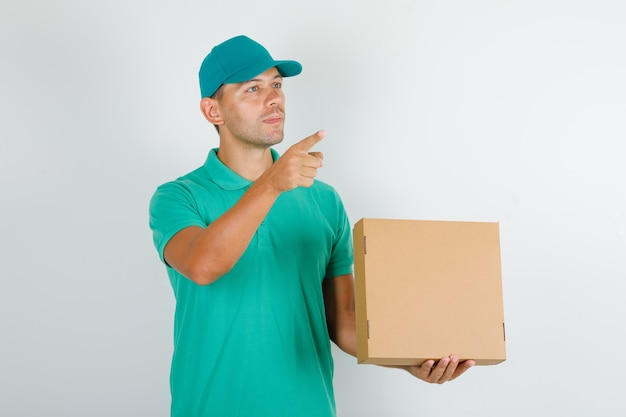 Курьер в зеленой футболке и кепке показывает что-то с картонной коробкой
