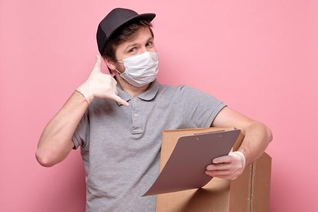 電話ジェスチャーを示すカードボックスを保持している医療用マスクの配達人