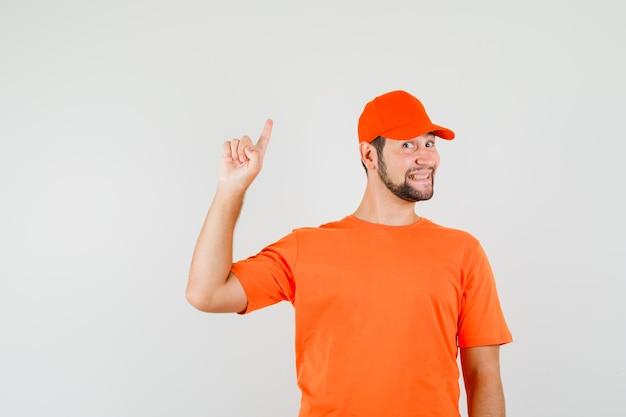 주황색 티셔츠를 입은 배달원, 모자가 손가락을 가리키고 즐거워 보이는 앞모습.
