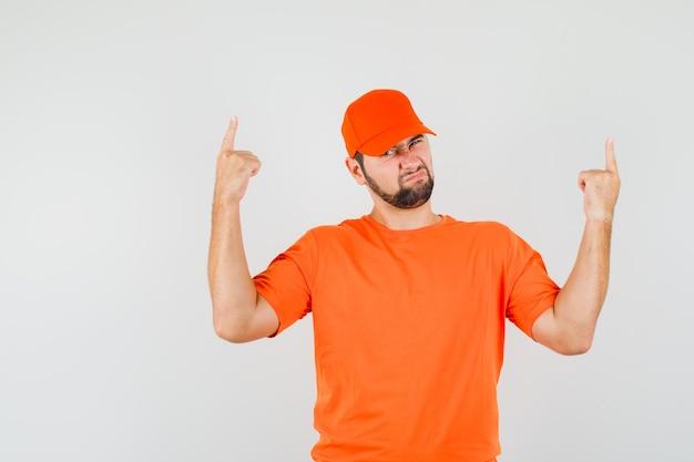 주황색 티셔츠를 입은 배달원, 모자를 위로 가리키고 희망이 없어 보이는 앞모습.