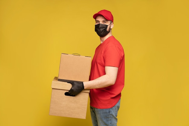 黄色の壁に隔離されたスタジオのボックスと保護マスクと手袋の配達人