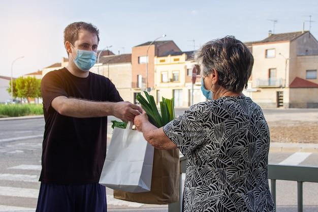 Курьер в защитной маске и медицинских перчатках доставляет покупку пожилой женщине. служба доставки под карантин,