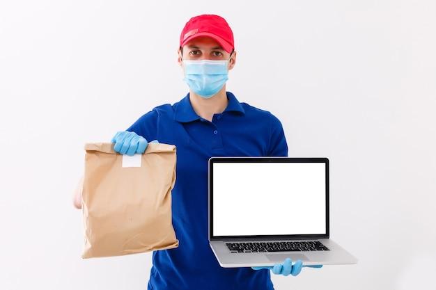 白い背景で隔離の赤い帽子の空白のtシャツ制服マスク手袋の配達人、ガイの従業員の仕事はラップトップコンピューターを保持し、サービス検疫パンデミックコロナウイルスウイルス2019-ncovコンセプト