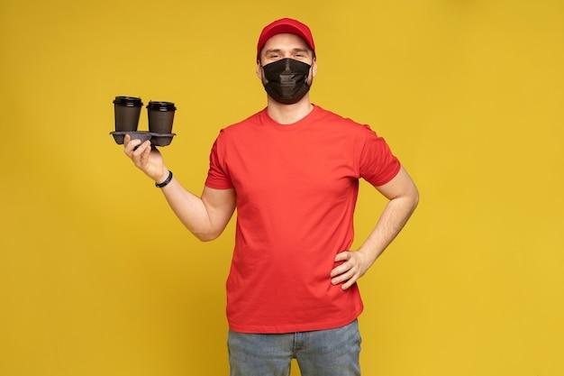 黄色の壁に分離された赤い帽子の空白のtシャツ制服マスク手袋の配達人