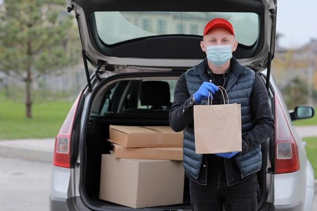 Курьер в красной кепке, медицинской маске и перчатках держит бумажный пакет возле автомобиля на открытом воздухе