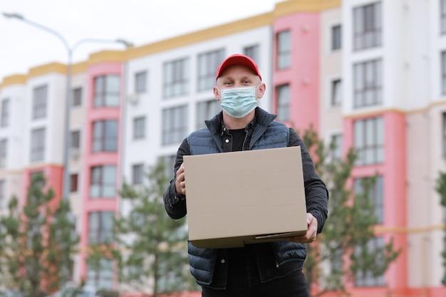 赤い帽子の配達人、顔の医療マスクは屋外で空の段ボール箱を保持します