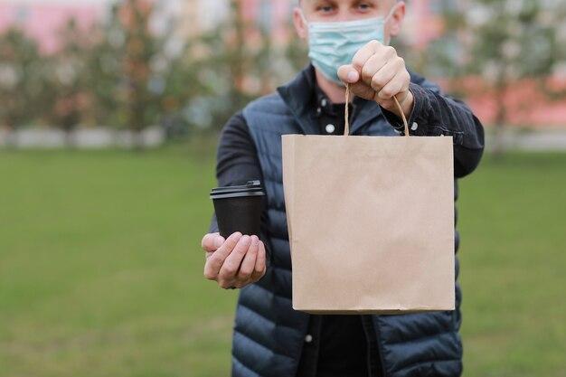 Доставщик в красной кепке, медицинская маска для лица, держащая бумажный пакет на вынос, и напиток в одноразовой чашке