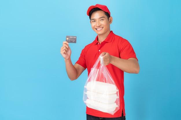 Доставщик в красной форме рубашки поло, стоящий с заказом еды с помощью кредитной карты