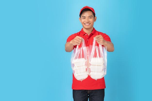 Доставщик в красной форме рубашки поло, стоящий с заказом еды