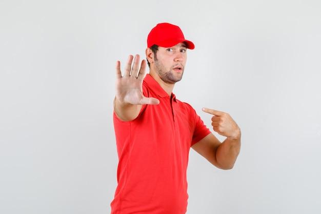 赤いtシャツの配達人、ジェスチャーなしで自分自身を指しているキャップ