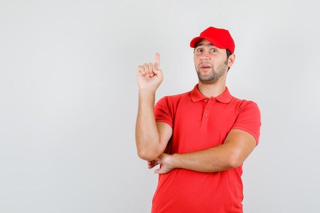 赤いtシャツの配達人、指を上に向けてキャップ