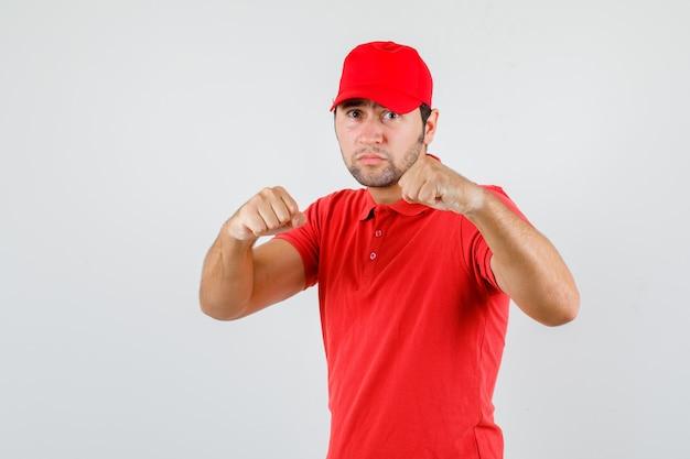 赤いtシャツ、ボクサーのポーズで立って、強く見えるキャップの配達人