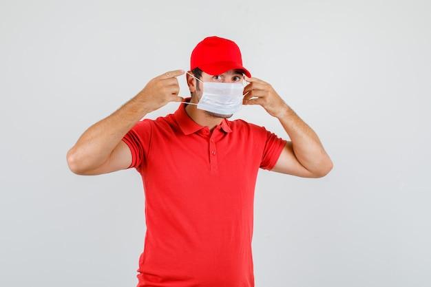 Доставщик в красной футболке, кепке в медицинской маске и осторожно смотрит